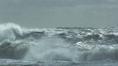 Storm waves breaking against rocks on ocean shoreline - stock footage