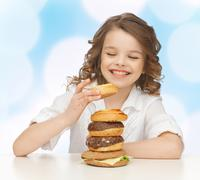 Happy smiling girl with junk food Stock Photos
