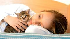 Girl stroking tabby kitten Stock Footage