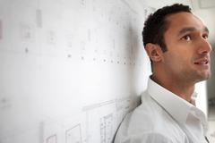 Serious Hispanic businessman leaning against blueprint Stock Photos