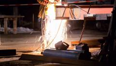 Welder welds structural beams at night - stock footage