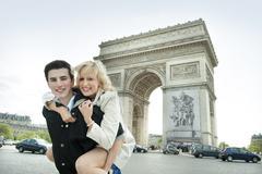 Caucasian man giving girlfriend piggyback ride near Arc de Triomphe Stock Photos