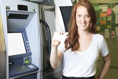 A student using a ATM machine at school - stock photo