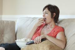 Caucasian woman eating popcorn and watching television Stock Photos