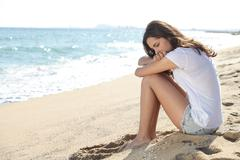 Portrait of a worried girl sitting on the beach - stock photo