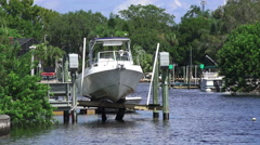 Boat Of Dock Lift On Florida River With Trees Stock Footage