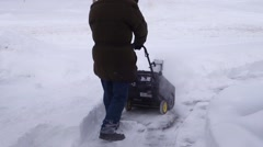 Clearing driveway using a snow blower Canadian winter Stock Footage