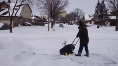 Man using a snow blower Stock Footage