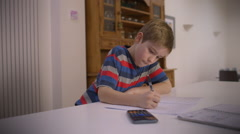 Young boy concentrating on his homework and asks his father for help - stock footage