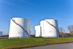 white tanks in tank farm with blue sky - stock photo