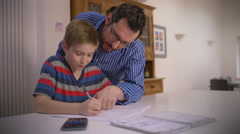 Father helps his young son with homework Stock Footage
