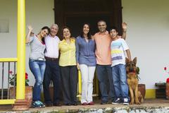 Hispanic family standing on porch together Stock Photos