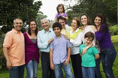 Smiling Hispanic family standing together Stock Photos