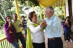 Hispanic family watching senior parents dancing Stock Photos