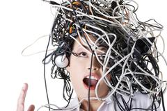 Troubled businesswoman with cables on head - stock photo