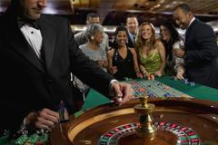 Excited friends gambling at roulette table in casino Kuvituskuvat