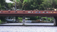 Cars Drive Across River Bridge With Boat Docks On River In Background Stock Footage