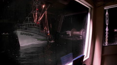A boat bobs in the water, then begins to move, as seen through the window of - stock footage