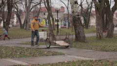 Male gypsy pushing trolley for transport and two little kids playing in the park Arkistovideo