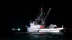 A fishing boat equipped with a net and a winch is working at night. Stock Footage
