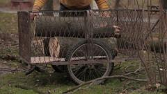 Poor man and woman gypsy putting firewood and branches for heating in trolley. Stock Footage