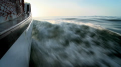 A boat moves along, churning up the water. - stock footage