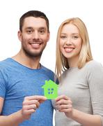Smiling couple holding green paper house Stock Photos