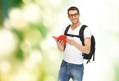 travelling student with backpack and book - stock photo