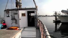 A boat passes through a marina where many boats are docked. Stock Footage