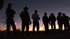 Stock Video Footage of In the early morning hours, seven or eight men are standing around holding