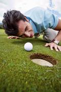 Hispanic man looking at golf ball near cup Stock Photos