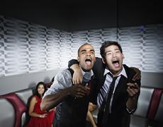 Friends singing karaoke in nightclub Stock Photos