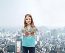 smiling little girl giving dollar cash money - stock photo