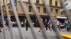 Australian crowds on crosswalk through bars rack focus Stock Footage