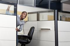 Mixed race businessman peering out from office cubicle Stock Photos