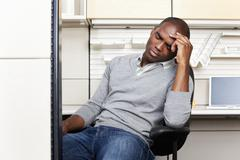 Frustrated mixed race businessman sitting in office cubicle Stock Photos