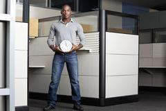 Mixed race businessman holding clock in office cubicle Stock Photos