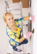 Smiling woman in gloves doing renovations at home Stock Photos
