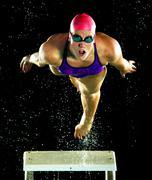 Caucasian swimmer diving off starting block Kuvituskuvat