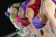 Swimmers preparing to dive off starting blocks Kuvituskuvat