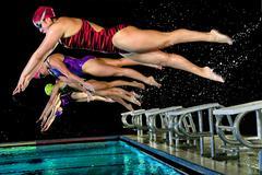 Swimmers diving off starting blocks Kuvituskuvat