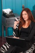 Redhead Woman Sitting Office Setting Working Computer Laptop - stock photo