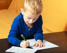 Blond boy child kid with pen writing on piece of paper. At home. - stock photo
