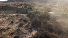 A vehicle travels up a road bordered by a tall fence. Stock Footage