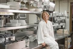 Caucasian chef sitting in commercial kitchen Stock Photos
