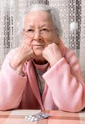 Old sad woman with pills at home - stock photo