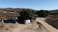 Campers are parked under a tree in a remote area. Stock Footage
