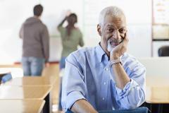 Black teacher sitting in classroom Kuvituskuvat