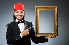 Man with fez  hat and picture frame - stock photo