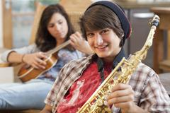 Mixed race teenagers playing musical instruments Stock Photos
